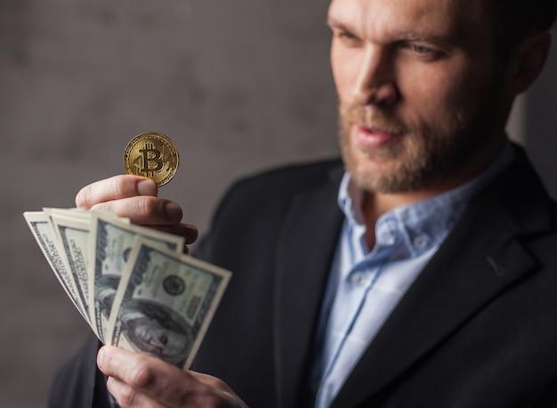 Mann, der geld und bitcoin hält. fokus auf münze
