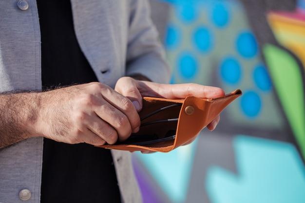 Mann, der geld von seiner brieftasche nimmt