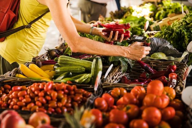 Mann, der gemüse vom gemüsestand am supermarkt wählt