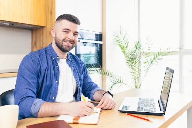 Mann, der geschäfte macht, während er zu hause bleibt, in der küche am tisch sitzt und einen laptop benutzt