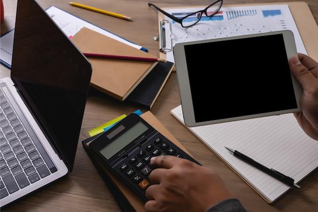 Mann der geschäftslaptop-mannhand, die an laptop-computer auf hölzernem schreibtisch laptop mit leerem bildschirm auf tabellenbildschirm arbeitet