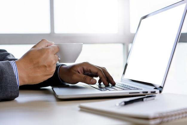 Mann der geschäftsmannhand, die an laptop-computer leerem laptop des weißen schirmes arbeitet