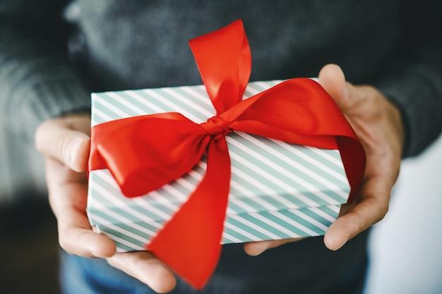 Mann, der geschenk mit rotem band hält