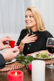 Mann, der geschenkbox mit ring überraschter frau am tisch darstellt