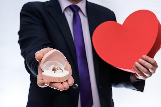 Mann, der geschenkbox mit ring und rotem herzen anbietet