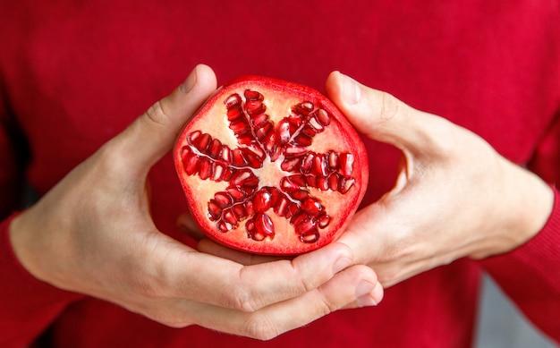 Mann, der geschnittenen reifen granatapfel hält und zeigt. granatapfelfrüchte sind reich an zucker, tanninen und vitamin c.