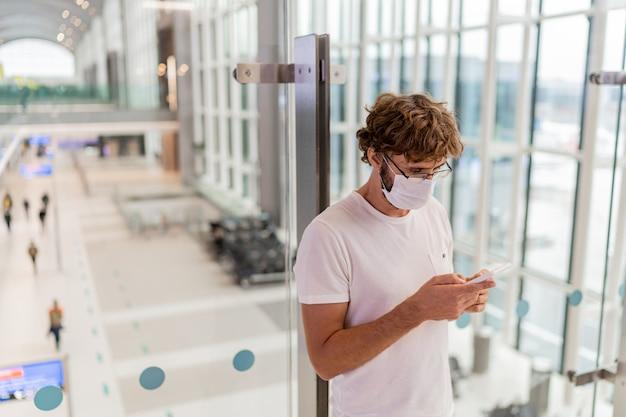 Mann, der gesichtsmaske im flughafen und im smartphone trägt