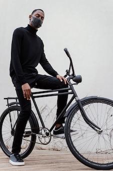 Mann, der gesichtsmaske trägt und sein fahrrad reitet
