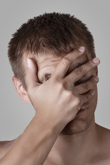 Mann, der gesichtspalme tut oder seine augen und gesicht mit handfläche bedeckt