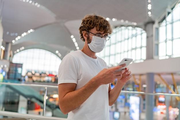 Mann, der gesichtsschutzmaske unter verwendung des smartphones trägt