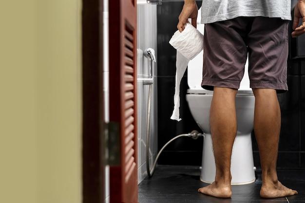 Mann, der geweberolle in der toilette seines hauses hält