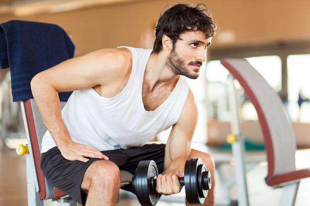 Mann, der gewicht im fitnessstudio hebt