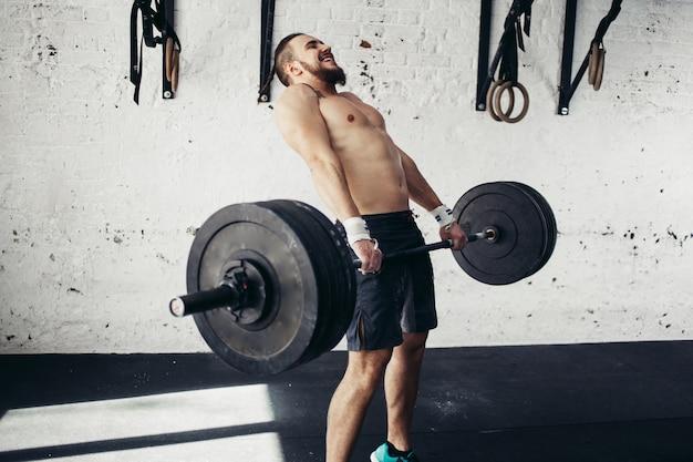 Mann, der gewichte hebt. muskelmann-training im fitnessstudio, das übungen mit langhantel macht