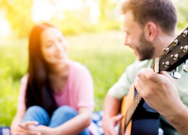 Mann, der gitarre auf picknick spielt
