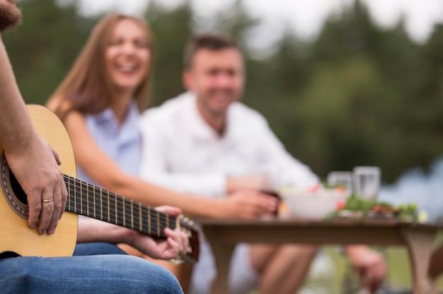 Mann, der gitarre draußen mit freunden an einem grill spielt