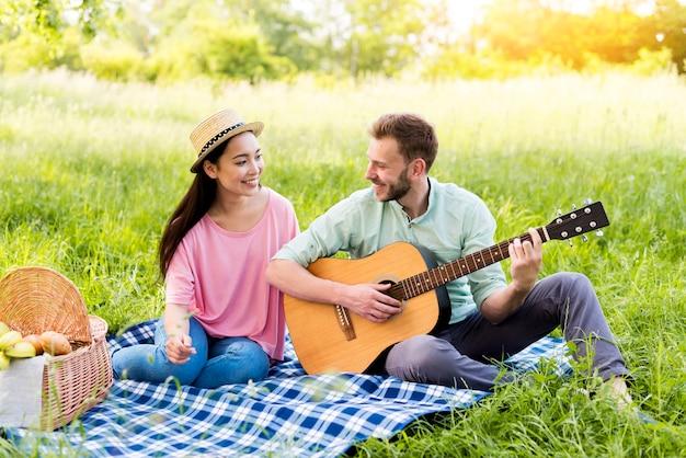Mann, der gitarre für frau spielt