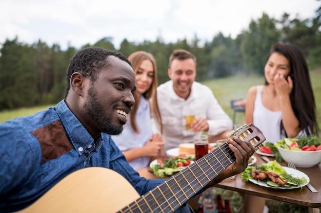 Mann, der gitarre für seine freunde an einem grill spielt