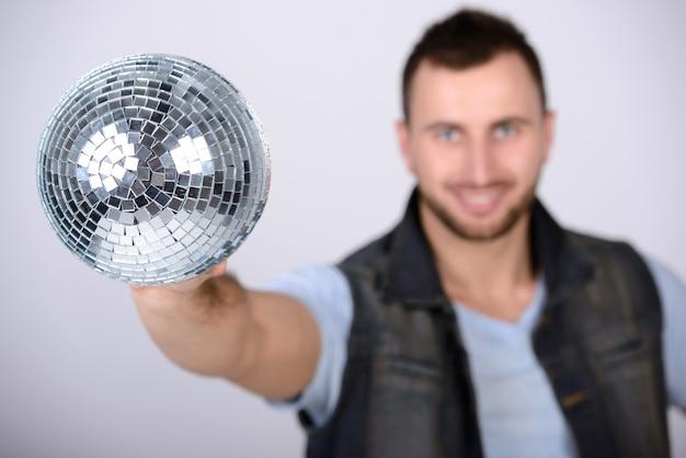Mann, der glänzenden ball der disco zeigt