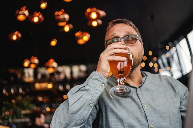 Mann, der glas des kalten frischen hellen biers trinkt, während in der bar nach der arbeit sitzt.