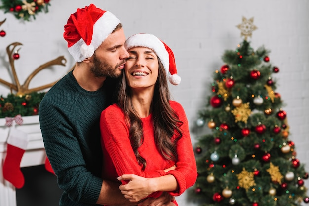 Mann, der glückliche frau im weihnachtshut küsst
