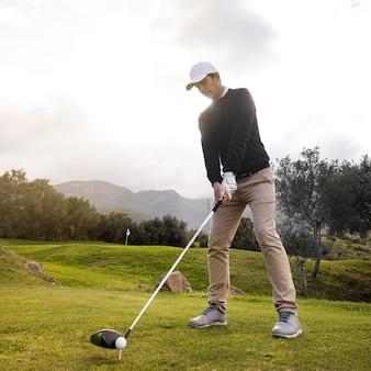 Mann, der golf auf dem feld mit verein spielt