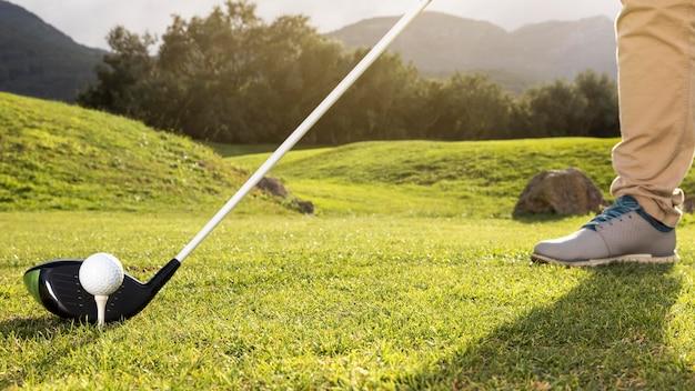 Mann, der golf auf dem feld übt