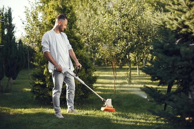 Mann, der gras mit rasenmäher im hinterhof schneidet. mann in einem hemd.