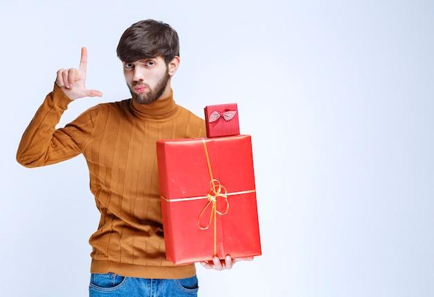 Mann, der große und kleine rote geschenkboxen hält und die größe in der hand zeigt.