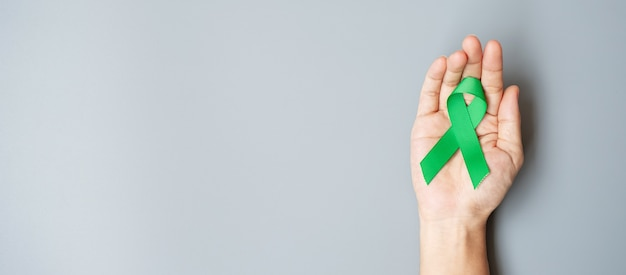 Mann, der grünes band für das unterstützen des lebenden lebens und der krankheit hält.