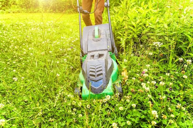 Mann, der grünes gras mit rasenmäher im hinterhof schneidet. gartenland lifestyle-tabelle