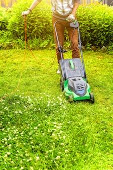 Mann, der grünes gras mit rasenmäher im hinterhof schneidet. hintergrund des gartenlandeslebensstils.