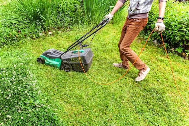 Mann, der grünes gras mit rasenmäher im hinterhof schneidet. hintergrund des gartenlandeslebensstils