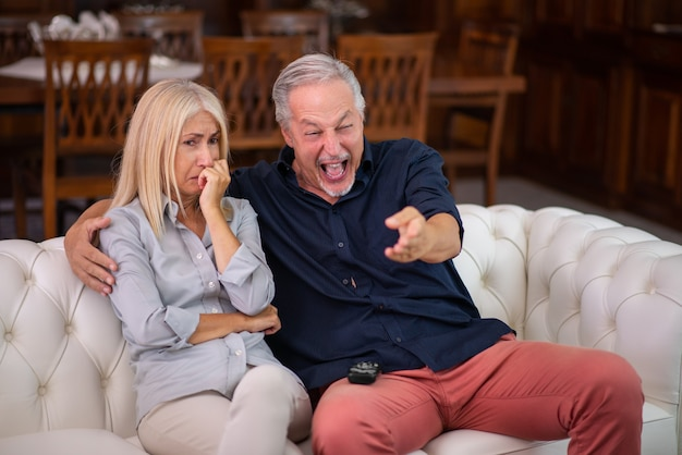 Mann, der gut lacht, seine frau weint, während er das gleiche fernsehprogramm sieht, mangel an empathiekonzept