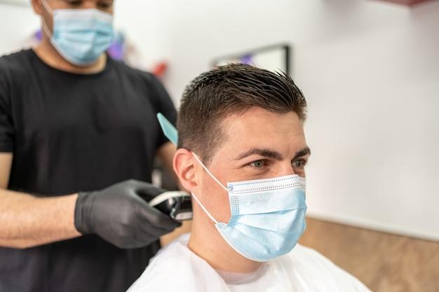 Mann, der haarschnitt an der barbershop-tragenden maske erhält.