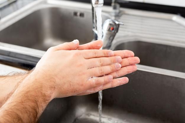 Mann, der hände mit antibakterieller seife und wasser in metallspüle für coronavirus-prävention wäscht. hand hygiene.