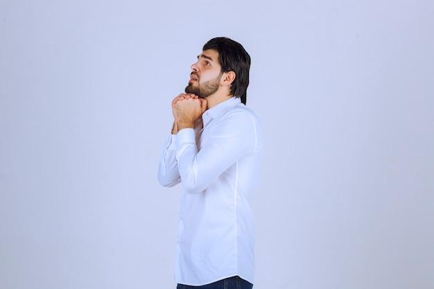 Mann, der hände vereint, betet und für etwas träumt.