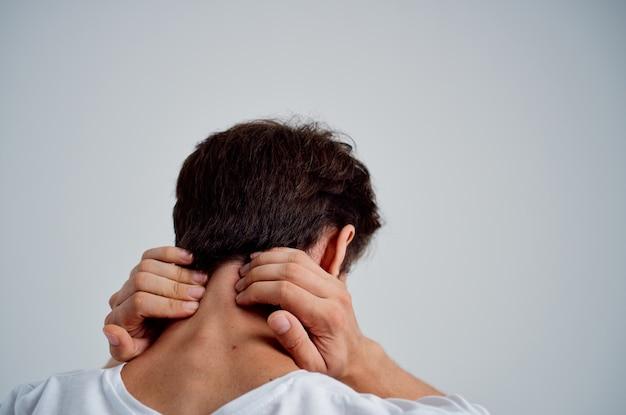 Mann, der hals-arthritis-gesundheitsprobleme heller hintergrund hält. foto in hoher qualität