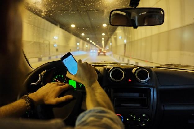 Mann der hand, der smartphone beim fahren des transport- und fahrzeugkonzeptes des selektiven fokus des autos verwendet