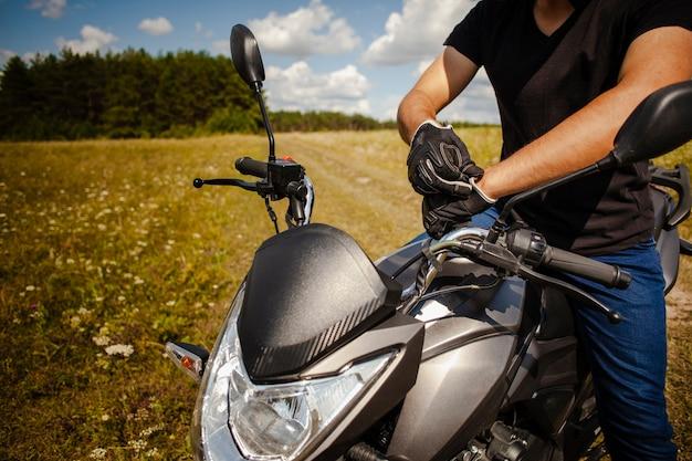 Mann, der handschuhe auf motorrad anzieht