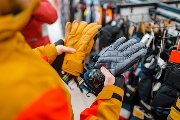 Mann, der handschuhe für ski oder snowboarden anprobiert