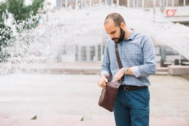 Mann, der handtasche an der straße überprüft