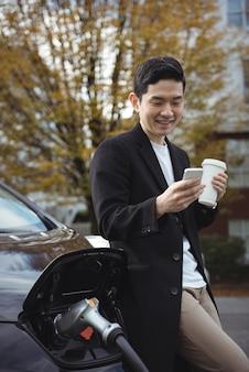 Mann, der handy beim aufladen des autos verwendet