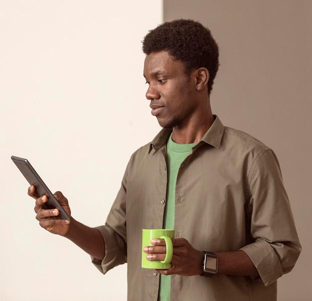 Mann, der handy benutzt und einen grünen becher hält