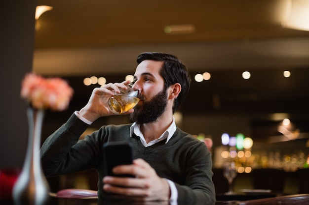 Mann, der handy hält und etwas trinkt