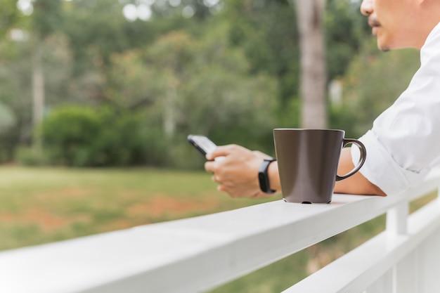 Mann, der handy mit kaffeetasse auf balkon in gartenansicht verwendet.