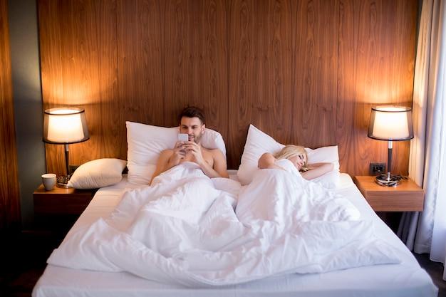 Mann, der handy während frau schläft im bett verwendet