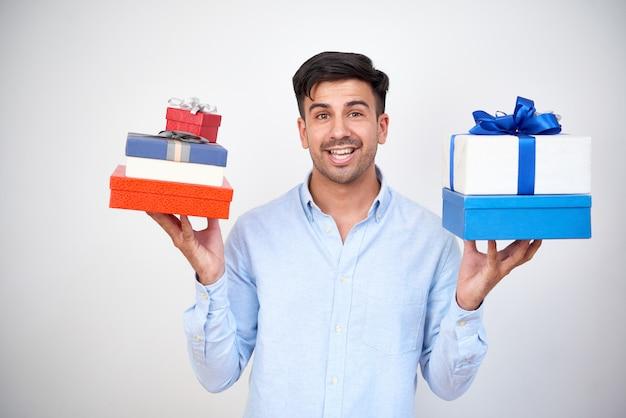 Mann, der haufen von geschenken hält