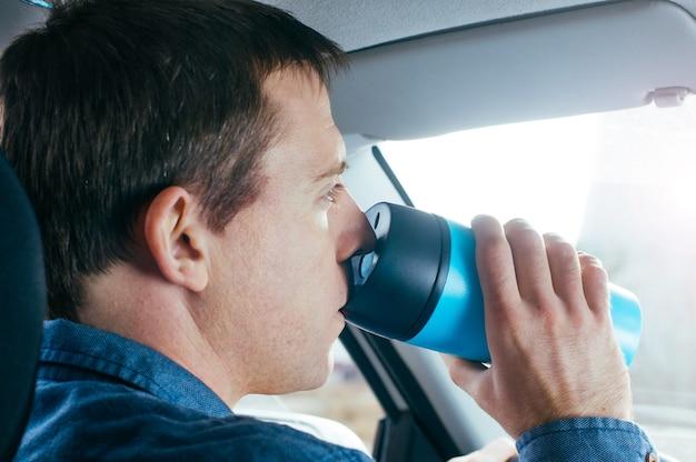 Mann, der heißen kaffee vom thermobecher in einem auto trinkt