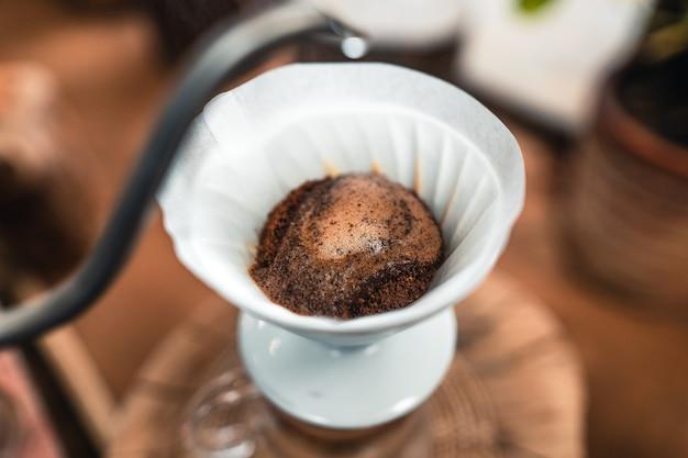 Mann, der heißes wasser in den kaffeetropfer über dem glasgefäß hinzufügt.