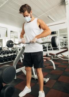 Mann, der herausarbeitet, während er medizinische maske im fitnessstudio trägt